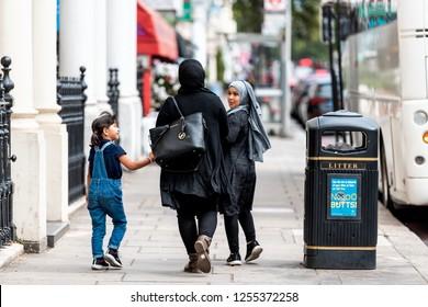 London, UK - September 16, 2018: People arab muslim family walking with woman in hijab clothing on sidewalk street with children in Kensington