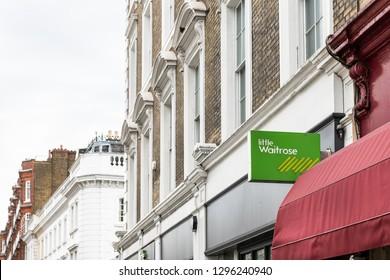London, UK - September 16, 2018: Neighborhood local store little Waitrose upscale expensive green sign grocery shopping storefront facade exterior entrance closeup in Kensington