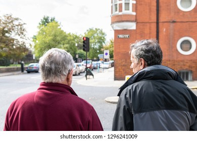 London, UK - September 16, 2018: Back of two men pedestrians waiting for red traffic light on street road in morning in Pimlico or Chelsea
