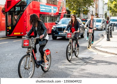 London, UK - September 16, 2018: Many people pedestrians on bicycles riding by traffic on bikes street road in center of downtown Santander rental
