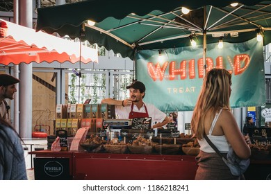 London, UK - September 17, 2018: People buying artisan fudge from a market stand in Borough Market, one of the largest and oldest food markets in London.