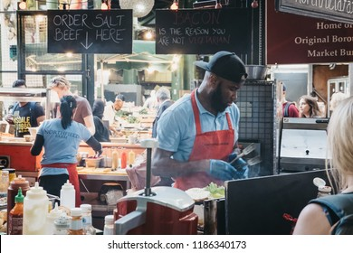 London, UK - September 17, 2018: Staff preparing food at Northfield Butchery market stand in Borough Market, one of the largest and oldest markets in London, UK.