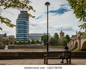 London / UK - September 18 2018: An unidentified woman sits on a bench by Putnam bridge. The St Mary`s Church is on the right and the Putney Wharf Tower on the left.
