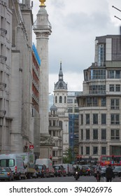 LONDON, UK - SEPTEMBER 19, 2015: City of London street with Monument, traffic and people crossing the road