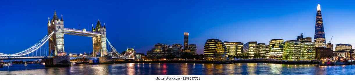 London, UK - September 2018: Night cityscape with Tower Bridge, the Shard and the city hall on Thames river banks