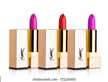 LONDON, UK - SEPTEMBER 21, 2017: Golden containers of luxury Yves Saint Laurent lipstick on white  background