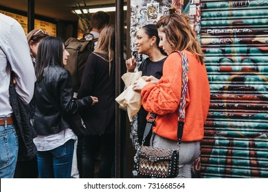 LONDON, UK - SEPTEMBER 24, 2017: People eating and queuing to buy bagels from a famous Beigel Shop in Brick Lane. The shop first opened in 1855 and sells fresh bagels 24 hours a day.