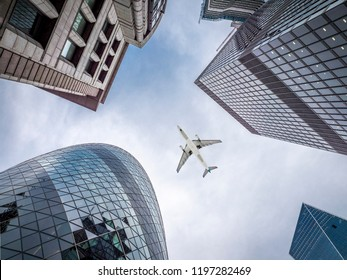 LONDON, UK - SEPTEMBER 25, 2018: the skyscrapers of London in the UK with a commercial airplane flying over them.