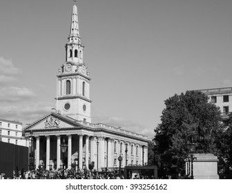 LONDON, UK - SEPTEMBER 27, 2015: Tourists in Trafalgar Square in front of St Martin in the Fields church in black and white