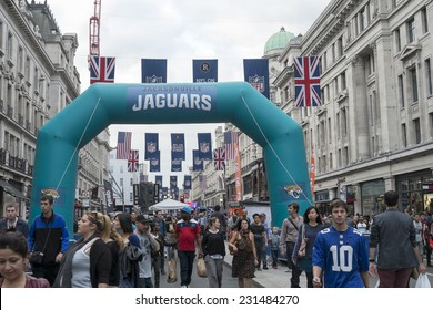 LONDON UK - SEPTEMBER 27: Crowded Regent street with Jaguars inflatable arch and NFL flags above. September 27 2014 in London. The street was closed to traffic to host NFL related games and events.