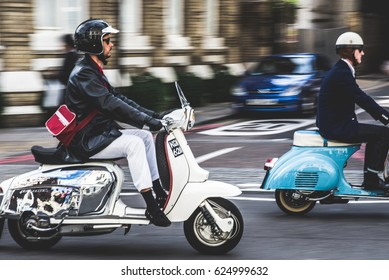 LONDON, UK - SEPTEMBER 28, 2015: Two scooters riding through the street of London.