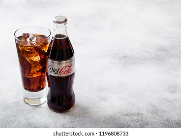 LONDON, UK - SEPTEMBER 28, 2018: Glass and bottle of Diet Coke Coca Cola soda drink with ice cubes and bubbles on stone kitchen background.