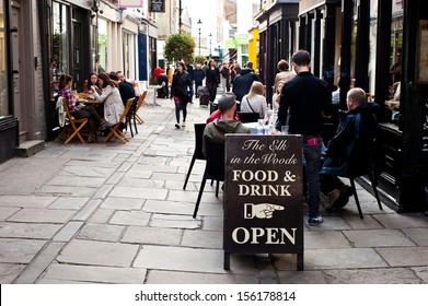 London, UK - September 29, 2013: People enjoy outdoor dining on the street at the Angel  The borough has one of the highest density of bars, restaurants and pubs in central London. Sign food and drink