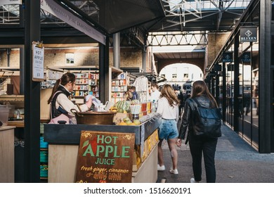 London, UK - September 7, 2019: People walking past Pink Grapefruit greengrocer at Spitalfields Market, one of the finest Market Halls in London with stalls offering fashion, antiques and food.