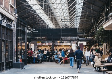 London, UK - September 7, 2019: People walking past stalls inside Spitalfields Market, one of the finest Market Halls in London with stalls offering fashion, antiques and food. Selective focus.