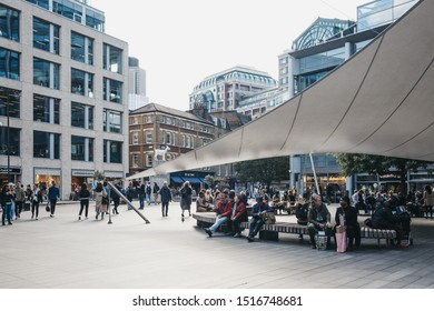 London, UK - September 7, 2019: People walking and relaxing outside Spitalfields Market, one of the finest Market Halls in London with stalls offering fashion, antiques and food. Selective focus.