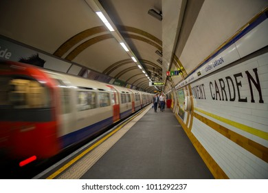 LONDON, UK, UNITED KINGDOM - JULY, 2016: Inside Covent Garden station platform with train passing and underground sign in London, UK. London Underground is the busiest metro system worldwide.
