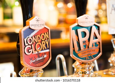 LONDON, UK, UNITED KINGDOM - JULY, 2016: Multiple brand beer tap dispenser in a London Pub with traditional beer brands: London Glory, Guinness, Greene King IPA.