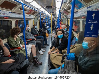 London. UK-10.29.2020: passengers on a London Underground train wearing face mask and social distancing as much as possible.
