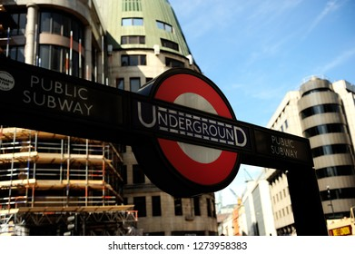LONDON, UK-22 AUG 2015: Underground train logo with blue sky and buildings in background in London England UK. The London Underground logo is one of the most recognized and imitated logos in the world