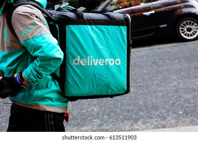 LONDON, UK-AUGUST 11, 2016. A cyclist delivery company Deliveroo speeding through city streets with a hot food delivery from take aways and restaurants to homes