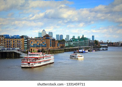 London UK-August 13th 2016:Charters boats navigating on Thames River along historic Wapping bank, looking east from the Tower Bridge to London Docklands on nice summer day