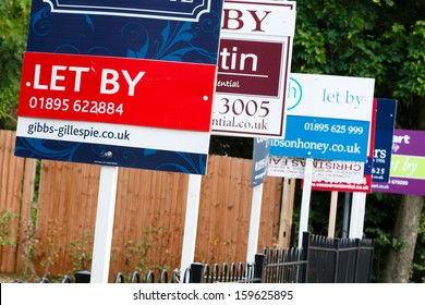 """London, UK-circa 2013: Estate agent """"let by"""" signs line the road in a suburb of London"""