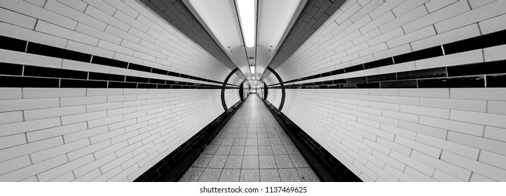 London Underground Tunnel Super Wide Angle of Tunnel Symmetrical Walkway with tiles on the ceiling and floor and walls lights above vanishing point in black and white monochrome 03 ‎November ‎2013