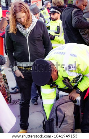 London, United Kingdom, 07th March 2018:-  Police search an unknown protester during the Stop The War Coalition's protest against the visit to the UK by the Crown Prince of Saudi Arabia