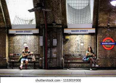 London, United Kingdom - 08-08-2018: two girls sitting and waiting for their train at Baker Street Tube station