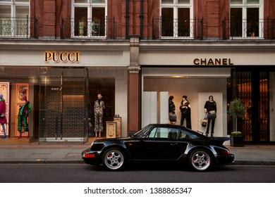 London, United Kingdom - 14/08/2018: A sporty-looking Porsche 911 (964) Turbo parking in front of the luxury brands Chanel and Pucci, on Sloane street, in London.