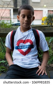 London, United Kingdom, 14th April 2018:- A young boy sits near the ruins of Grenfell tower ten months on from the devastating fire that killed 71