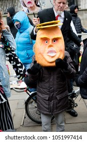 London, United Kingdom, 17th March 2018:- Kids try on a Donald Trump mask at the Stand Up to Racism march through central London