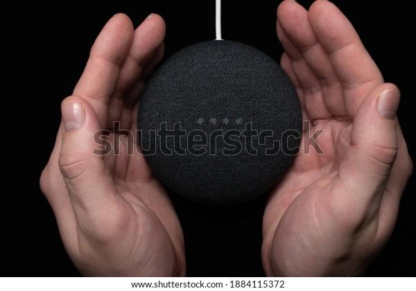 London, United Kingdom - 19 December 2020: Hands around a Google Nest Home Mini smart speaker with built-in Google Assistant on a black background.