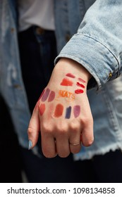 London / United Kingdom - 20 05 2018: young woman presents a selection of lipstick paints on her hand, OLYMPIC NATIONAL CENTRAL LONDON exhibition hall, Make-Up Artist Show - IMATS 2018