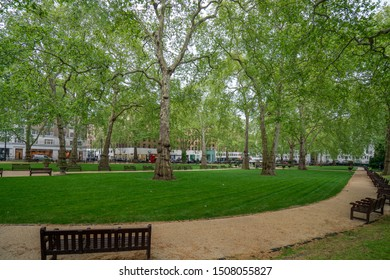 London, United Kingdom - 2019: Berkeley Square without people, green trees, empty banches.