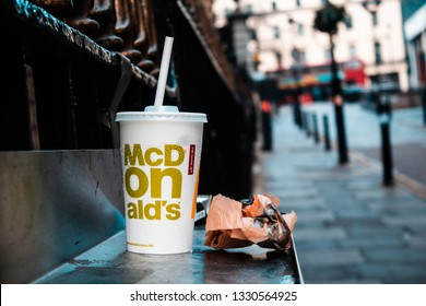 London / United Kingdom - 2.23.2019: McDonald's paper cup with a plastic straw, and a paper bag left on the street