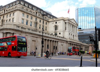 London, United Kingdom - 24 May 2017: Iconic red double-decker London bus passing by the iconic Band of England building