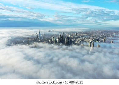 London, United Kingdom -28.11.2020: Aerial Drone Helicopter London City, The Shard Skyline, London Eye, The Gherkin, Cityscape, the roof of iconic skyscrapers is visible above the clouds and fog