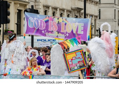 London, United Kingdom, 6th July 2019:- People at London Pride 2019 holding a banner reading God is Love