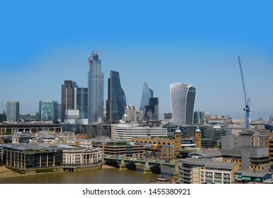 London, United Kingdom 6th July 2019: London business district skyline seen from south bank, river Thames in foreground on summer day