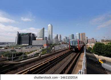 London, United Kingdom 6th July 2019: Canary Wharf skyline seen from Tower Hamlets, DLR Docklands Light Railway train in foreground on summer day, logos removed