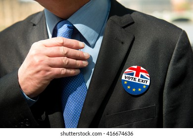 London, United Kingdom. 6th May 2016. EDITORIAL - Businessman in a dark business suit, wearing a VOTE EXIT pin badge and adjusting tie, for the fourth coming E.U. referendum election on 23rd May 2016.