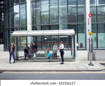 London, United Kingdom, 7 may 2017: several people wait at bus stop in canary wharf in london