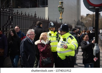 London, United Kingdom, April 13th 2019:- Two police officers helping people outside Westminster Parliament of UK