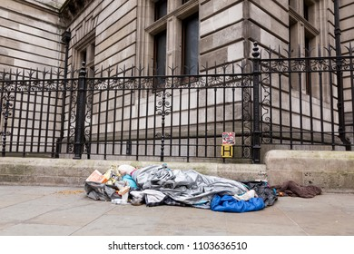 London, United Kingdom, April 15, 2018: A homeless man sleeps on the pavement near National Museum in the centre of London. Homelessness is considered a major and growing social problem in the UK.