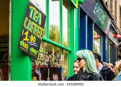 London, United Kingdom - April 30, 2017: Columbia Road Flower Sunday market. Tea and cofee shop, with beautiful lady with green hair looking at shop window