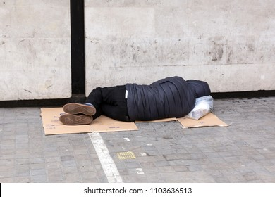 London, United Kingdom, April 7, 2018: A homeless man sleeps on the pavement near National Museum in the centre of London. Homelessness is considered a major and growing social problem in the UK.