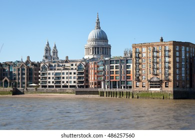 LONDON, UNITED KINGDOM - AUGUST 12, 2016: View of the dome of St Paul's Cathedral seen above modern buildings on the bank of the Thames River..