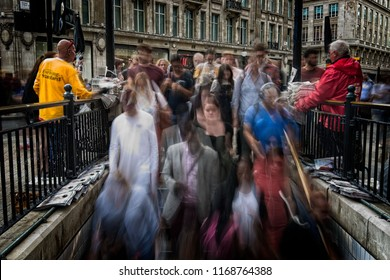 London, United Kingdom - August 18 2018: People rush to the Oxford Circus subway as the rush hour begins while newspaper distributors distribute free newspaper. Motion blur to create a sense of rush.